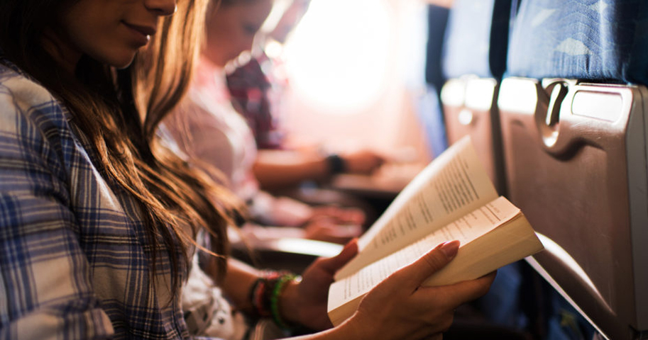 reading a book while travelling by airplane