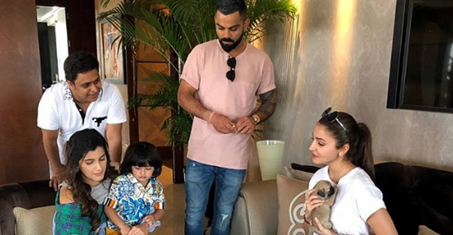 Anushka Sweetly Cuddles A Puppy As The Actress & Virat Engrossed In A Casual Meet With Friends